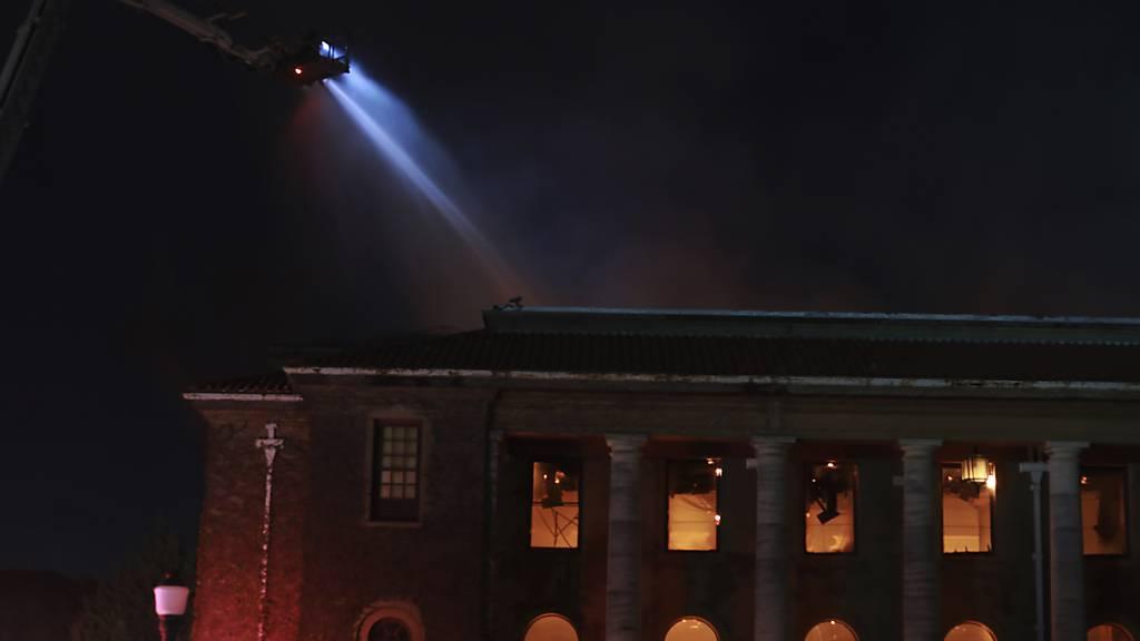 Feuerwehrleute löschen die Flammen in der  Jagger-Bibliothek an der Universität von Kapstadt. Ein Waldbrand, der an den Hängen vom Tafelberg wütete, griff auf die Universität über. Foto: Nardus Engelbrecht/AP/dpa