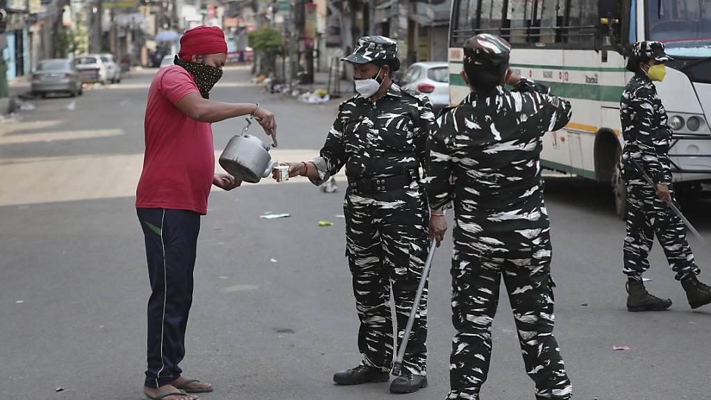 Ein Mann versorgt paramilitärisches Personal mit Trinkwasser. Indien hat zuletzt mehr als 343 000 Tagesneuinfektionen und 4000 Todesfälle in der gleichen Zeitperiode erfasst. Foto: Anupam Nath/AP/dpa