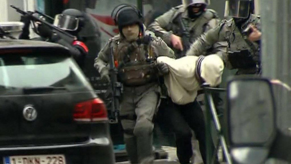 Sicherheitskräfte im Brüsseler Viertel Molenbeek führen einen Verdächtigen ab.