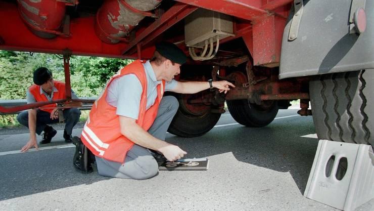 Polizisten kontrollieren Bremsen und Ladung von Lastwagen.