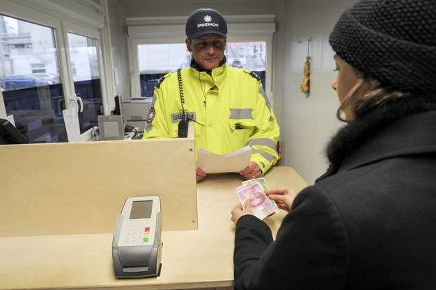 Bezahlen der Zollgebühren beim Schweizer Grenzwächter.
