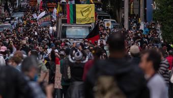 Demonstranten ziehen durch die Straßen. Der Protest fand statt, nachdem ein Mann vor einem Supermarkt in Porto Alegre von zwei Sicherheitsmännern niedergerungen und brutal geschlagen worden war. Der 40-Jährige erlag noch am Tatort seinen Verletzungen. Foto: Andre Lucas/dpa