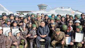 Nordkoreas Machthaber Kim Jong Un posiert mit Armeeangehörigen während Luftübungen der Streitkräfte.