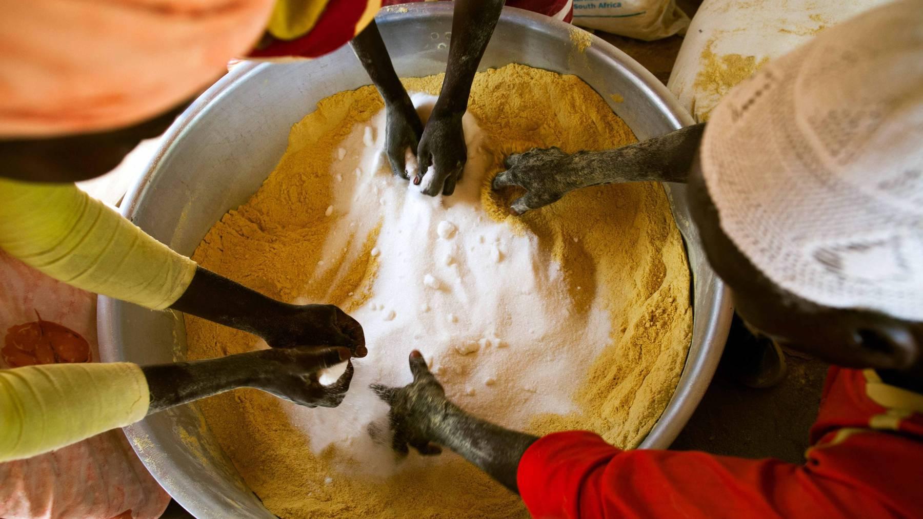 Freiwillige bereiten Essen für unterernährte Kinder in Sudan vor. Laut Caritas  wird die Zahl der Hungerleidenden künftig steigen. (Symbolbild)