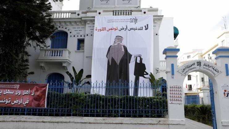 Die Journalistengewerkschaft SNJT entrollte an der Fassade ihres Büros in der Innenstadt von Tunis ein riesiges Plakat, das den saudischen Kronprinzen mit einer Kettensäge zeigt.
