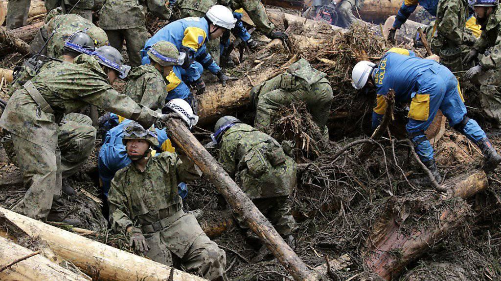Im Dorf Toho (Präfektur Fukuoka) suchen Rettungskräfte und Soldaten unter Schlamm, Geröll, Geäst und Baumstämmen nach Vermissten.
