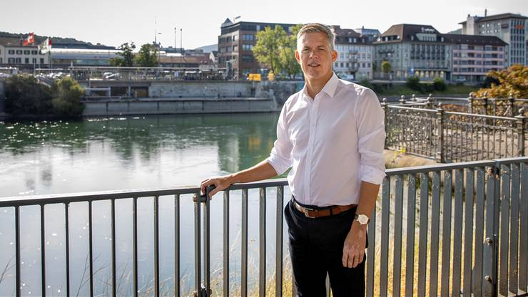 Wirtschaftsförderer Rolf Schmid posiert beim Amtshausquai vor den grossen Arbeitgebern in der Region Olten: SBB, Swisscom und Alpiq (v.l.). Bild: Patrick Lüthy