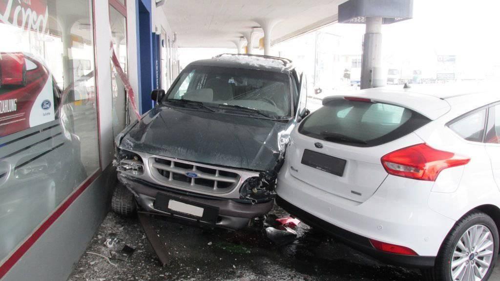 Nach der frontalen Kollision beschädigte ein Auto zusätzlich die Scheibe einer Garage und ein Ausstellungsauto.