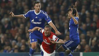 Arsenals Lukas Podolski kommt nach einem Tackling zu Fall.