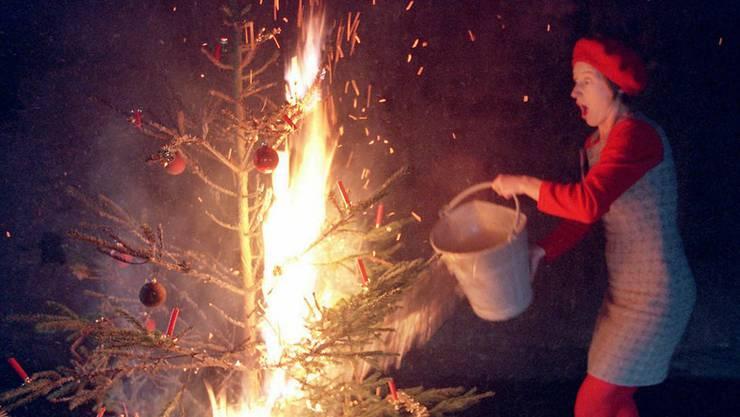 Eine Frau löscht einen brennenden Christbaum. Die Statistik zeigt, dass die Aargauer Polizei im Dezember am meisten Brände meldet.