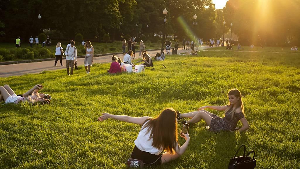 Menschen genießen das warme Wetter im Gorki-Park während des Sonnenuntergangs. Die Behörden in Moskau haben die Ende März wegen des Ausbruchs des Coronavirus eingeführten strengen Sperrmaßnahmen gelockert. Foto: Alexander Zemlianichenko/AP/dpa