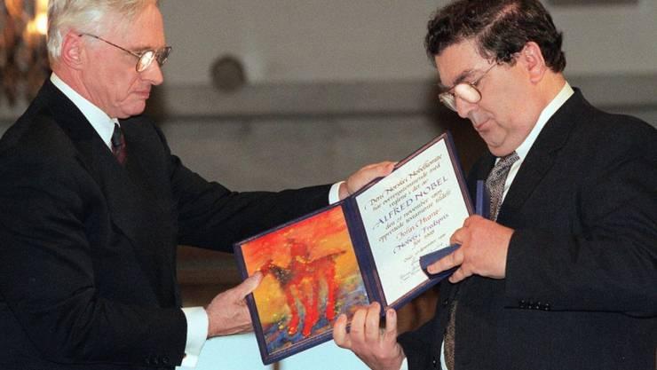 ARCHIV - John Hume (r), ehemaliger Vorsitzender der Social Democratic and Labour Party (SDLP), schaut auf das Friedensnobelpreisdiplom, das er von Francis Sejersted, damals Vorsitzender des norwegischen Friedensnobelpreiskomitees, während der Verleihungszeremonie im Osloer Rathaus erhielt. Foto: Bjoern Sigurdsoen/NTB POOL/AP/dpa