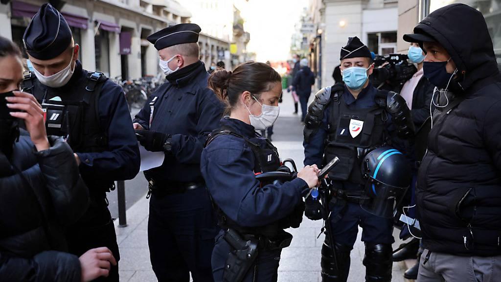 Polizisten kontrollieren Ausweise von Passanten in Paris. Foto: Thomas Coex/AFP/dpa
