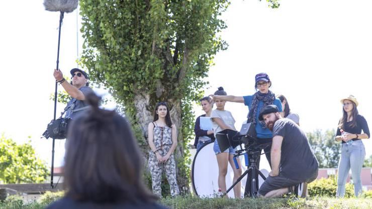 Michèle Bachmann (blaues T-Shirt) bespricht mit einer Schülerin die Szene. Kameramann Adrian Ehrbar (r.) gibt ebenfalls Tipps.