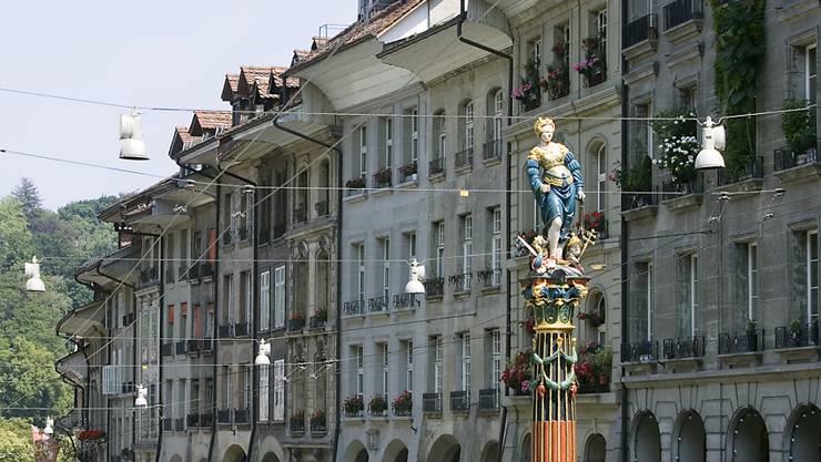 Der Gerechtigkeitsbrunnen in der Berner Altstadt. Die Brunnenfigur ist eine Statue der Justitia mit verbundenen Augen, die in der linken Hand die Waage trägt und mit der rechten Hand das Richtschwert erhebt.
