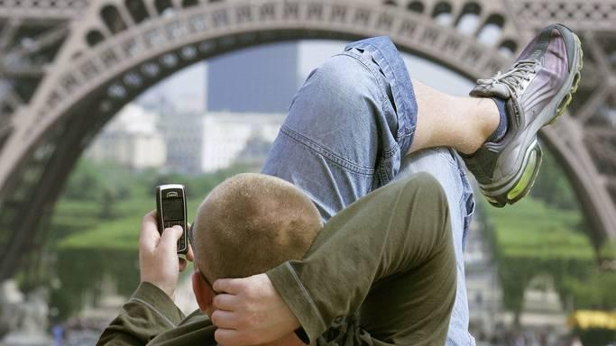 Ein Mann bedient sein Telefon vor dem Eiffelturm. Auch in Frankreich wird mitgelesen. (Symbolbild)