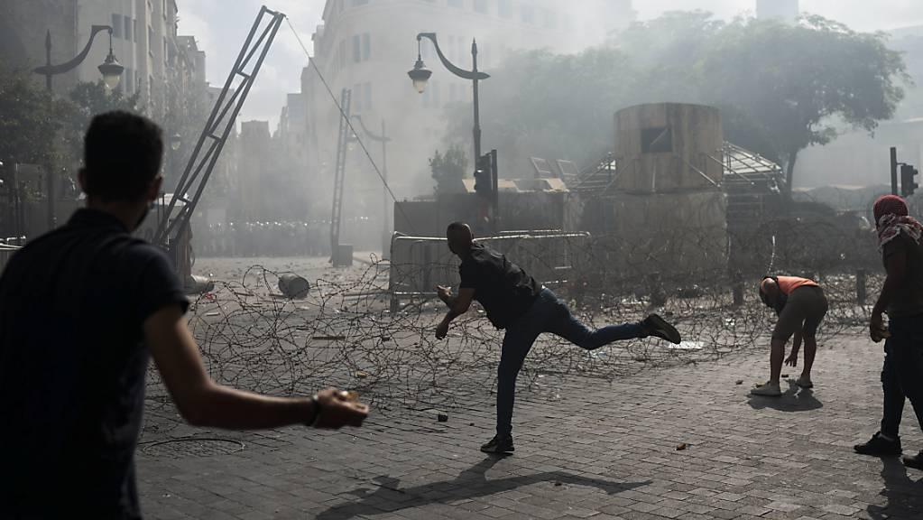 Demonstranten werfen Steine auf Polizisten. Foto: Felipe Dana/AP/dpa