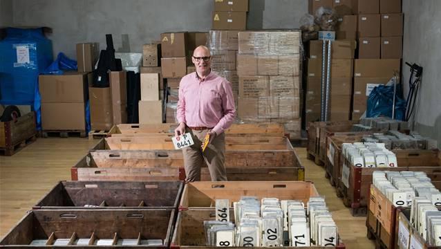 Frank Müller sitzt mitten in der Nummernschilder-Sammlung.