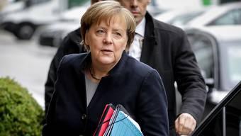 """Buchstäblich erschöpfende Gespräche - Kanzlerin Merkel mit Vorschlägen für eine """"Jamaika""""-Koalition unter dem Arm."""