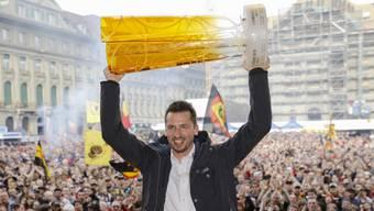 SCB-Trainer Lars Leuenberger hält den Meisterpokal hoch und lässt sich von der Menschenmenge auf dem Bundesplatz feiern.