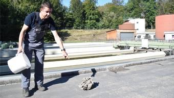 Klärmeister Urs Jäggi mit einem Klumpen aus Öl, Fett und Feststoffen, der aus einer verstopften Pumpe geholt wurde.