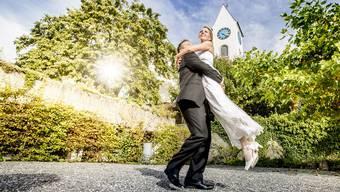 Andrea und André Zehnder sind schon verheiratet. Für die Broschüre der reformierten Landeskirche posieren sie vor der Kirche Kirchberg. André Scheidegger