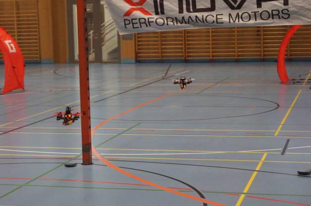 Multicopter im Tiefflug durch den Trainingsparcours in der Turnhalle.
