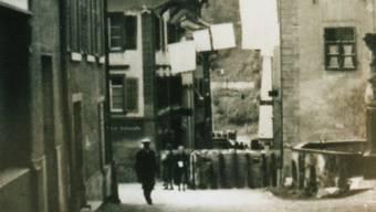 Die untere Hauptstraße in Laufenburg im April 1945: Aus den Fenstern hängen zum Zeichen der kampflosen Übergabe der Stadt weiße Flaggen. Am Mittleren Brunnen sind Sandsackstellungen und an der Laufenbrücke eine Panzersperre zu erkennen.