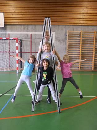Stolz präsentieren die Nachwuchstalente des Zirkus eine Pyramide auf der Leiter
