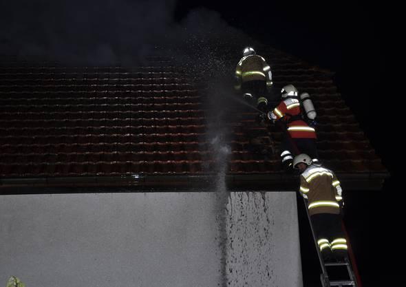 Die Feuerwehr verhindert, dass das Feuer auf das Nachbarhaus übergreift.