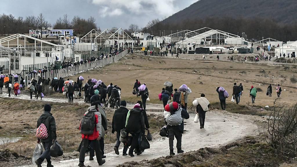 Migranten gehen am 30. Dezember 2020 mit ihren Habseligkeiten zurück zum Lager Lipa. Foto: Kemal Softic/AP/dpa