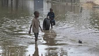 Somalische Kinder spielen in einer überfluteten Strasse im Süden Mogadischus