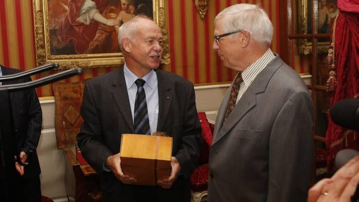 Felix Strässle (CEO Regio Energie) übergibt Heinz Uhlmann zum Dank ein Geschenk für die zahllosen Stunden, in denen er die Objekte instandstellte.  (Foto: Andreas Kaufmann)