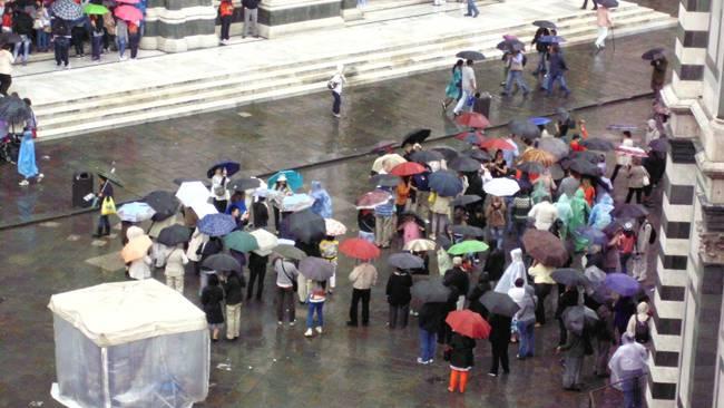 Touristen auf dem verregneten Domplatz von Florenz.