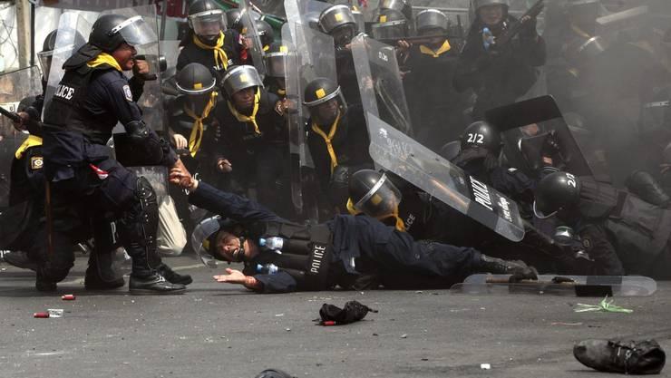 Polizisten räumen in Bangkok ein Lager der Demonstranten, dabei kommt es zu gewaltsammen Zwischenfällen.