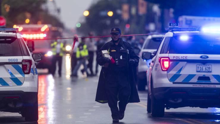Polizisten untersuchen den Tatort einer Schießerei. Infolge einer Schießerei in Chicago sind nach Angaben der Polizei 14 Menschen mit Verletzungen ins Krankenhaus gekommen. Foto: Tyler Lariviere/Chicago Sun-Times/AP/dpa