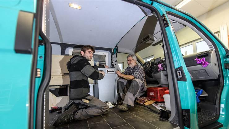 Rudolf und Sandro Bärtschi an der Arbeit: Sie bauen ein Lavabo in einen VW-Bus ein, der Bodenbelag und das Bett sind bereits montiert.