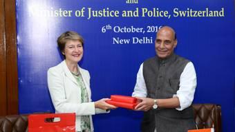 Bundesrätin Simonetta Sommaruga und der indische Minister für Inneres, Rajnath Singh, tauschen nach der Unterzeichnung des Abkommens die Dokumente aus.