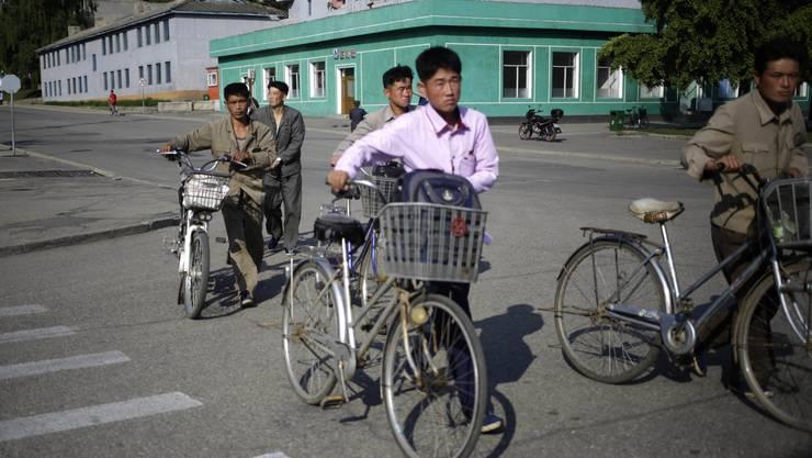 Männer stossen ihre Fahrräder über eine Strasse.