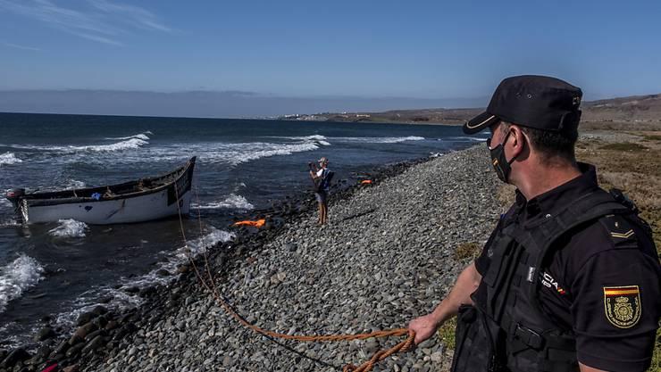 ARCHIV - Ein spanischer Polizist sichert ein Holzboot, mit dem Flüchtlinge aus Marokko nach der Fahrt über den Atlantischen Ozean auf den Kanarischen Inseln angekommen sind. Foto: Javier Bauluz/AP/dpa