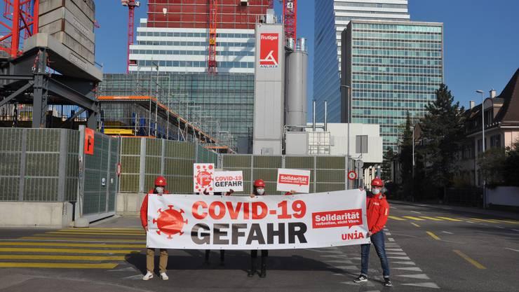 Unia-Gewerkschafter mit Plakat vor der Baustelle an der Grenzacherstrasse: Sie fordern die Schliessung der Roche-Baustelle.