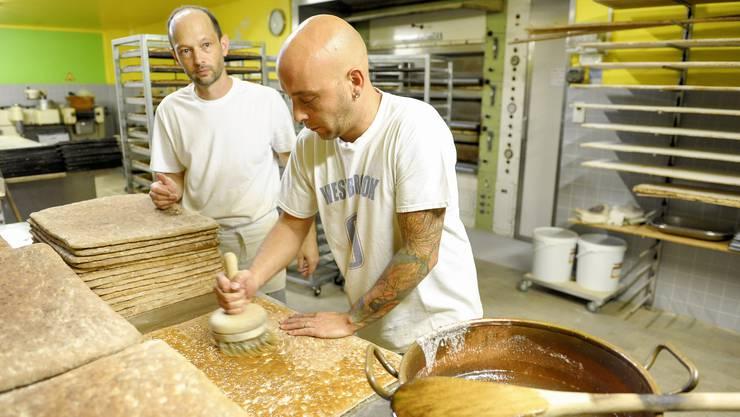 Die Bäcker Jean-Luc Kraemer (l.) und Franck Muller bestreichen die Läckerli-Platten mit einer Zuckerwasser-Glasur, bevor eine handbetriebene Sägemaschine die Platten in kleine Stücke sägt. i