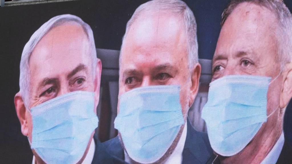 Grosse Qualition in Israel: Premierminister Benjamin Netanjahu, Rechtsaussen Avigdor Lieberman und Oppositionsführer Benny Gantz (von links) mit Mundschutz auf einem Plakat in Tel Aviv.