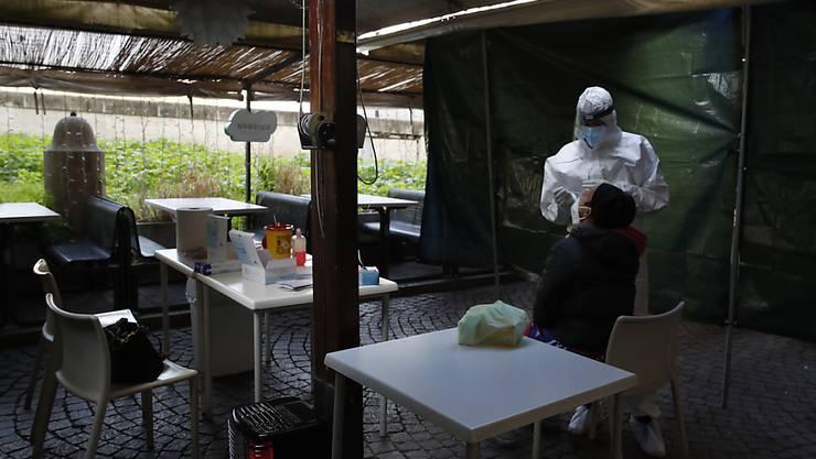 Eine Frau wird im Außenbereich eines geschlossenen Restaurants auf das Coronavirus getestet. Foto: Alessandra Tarantino/AP/dpa