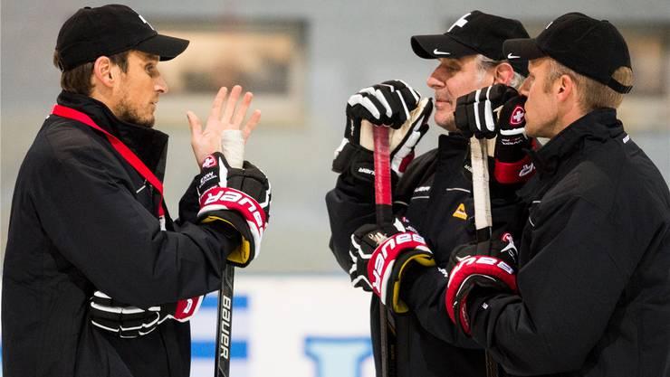 Patrick Fischer bespricht sich mit seinen Assistenten Felix Hollenstein und Reto von Arx (v. l.) während des ersten Trainings der Schweizer Eishockey-Nati.keystone