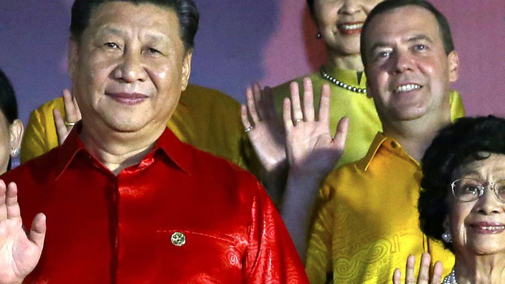 Bildfüllend und schwergewichtig am Apec-Gipfel: der chinesische Staats- und Parteichef Xi Jinping (links im roten Hemd), ganz der wirtschafltichen Bedeutung seines Landes entsprechend. Ebenso angemessen visuell vertreten: der russische Ministerpräsident Dmitri Medwedew (rechts oben im gelben Hemd).