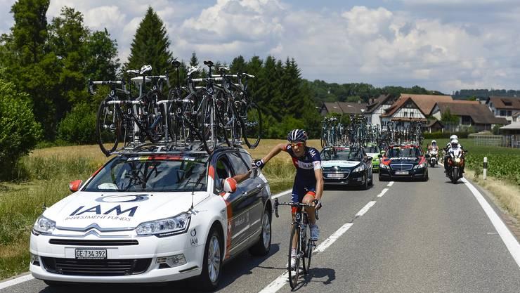 Der Schweizer Jonathan Fumeaux holt sich bei Marcello Albasini, sportlicher Leiter des Schweizer Teams IAM Cycling, am Teamfahrzeug während der fünften Etappe der Tour de Suisse 2014 von Ossingen nach Büren an der Aare einen neuen Bidon.
