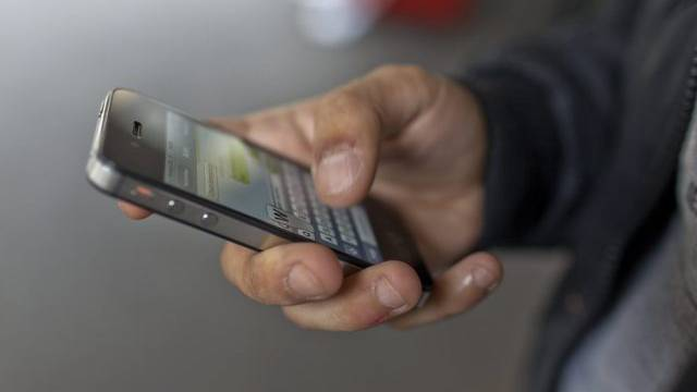 Ein Mann benutzt sein Smartphone (Symbolbild)