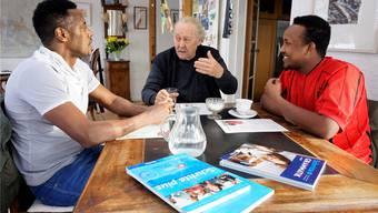 Samuel Schild unterrichtet Abdi Fatah (rechts) und Mattias Hailu in Deutsch.
