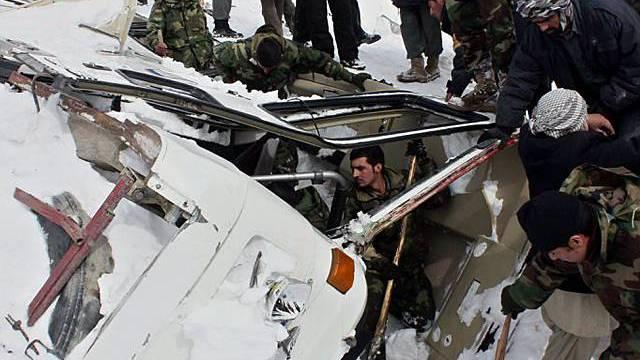 Rettungstrupps graben verschüttete Fahrzeuge aus